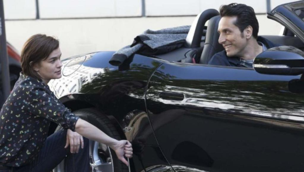 Damien (Vincent Elbaz) in the car with Alexandra (Marie-Sophie Ferdane) kneeling next to the car, fixing the tire.