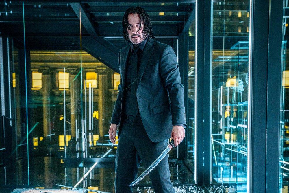 John Wick (Keanu Reeves) in a fighting stance, sword in hand.