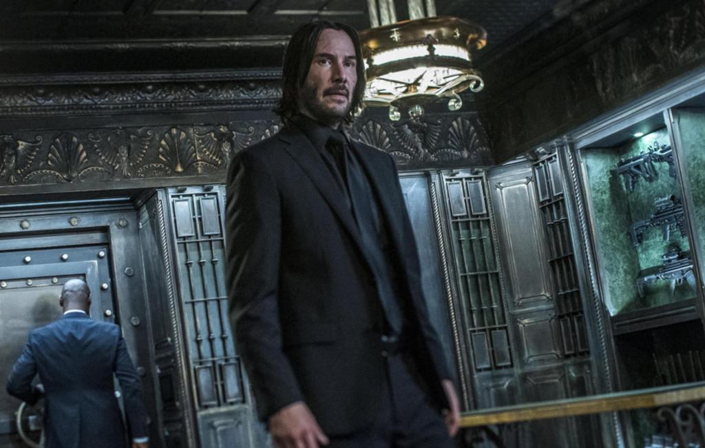 John Wick (Keanu Reeves) in a safe-like rooms filled with weapons.