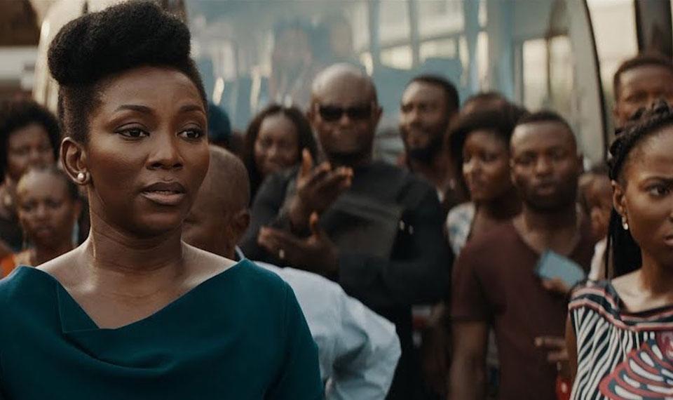 Adaeze (Genevieve Nnaji) in a crowd of people.