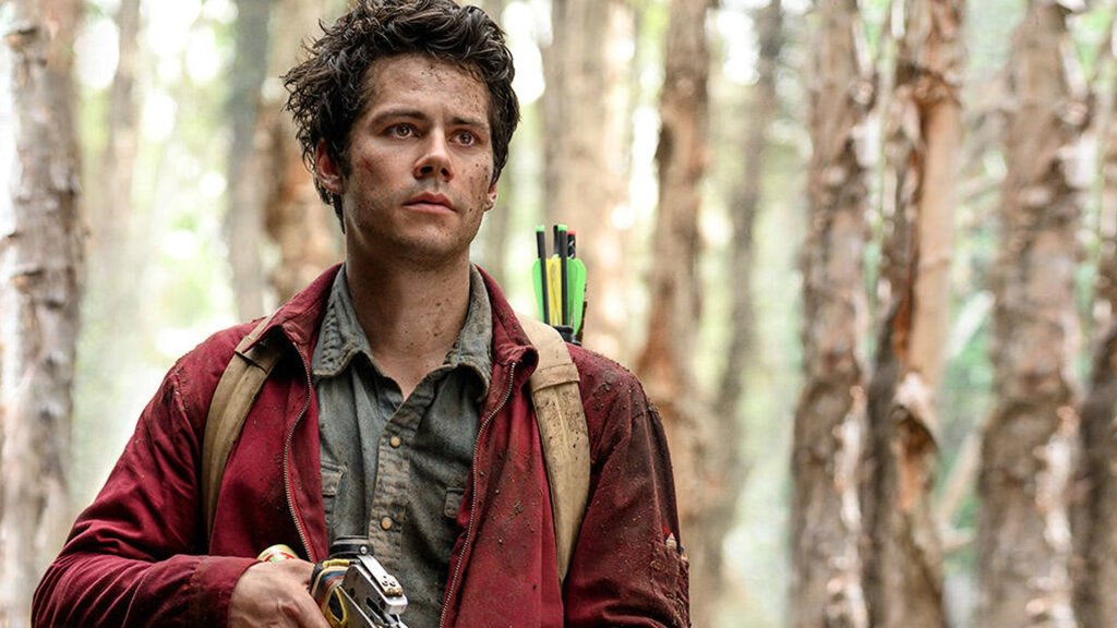 Joel (Dylan O'Brien) in the forsest, holding a crossbow.