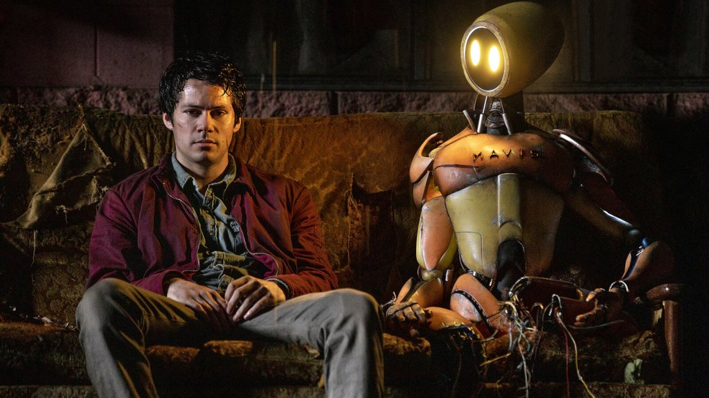 Joel (Dylan O'Brien) sitting on a desolate sofa next to a robot, looking despondent.