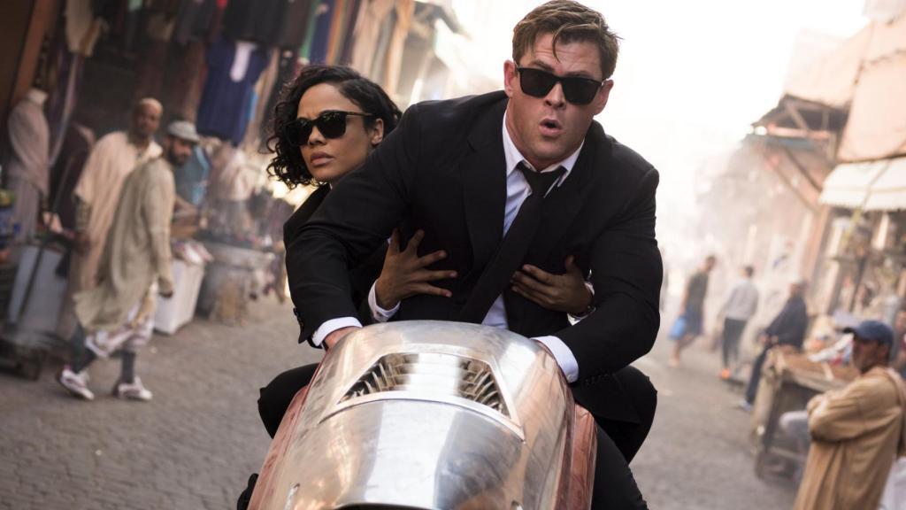 Agent M (Tessa Thompson) and Agent H (Chris Hemsworth) on a futuristic motorcycle.