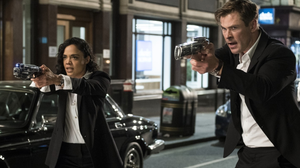 Agent M (Tessa Thompson) and Agent H (Chris Hemsworth) aiming their weapons at something.
