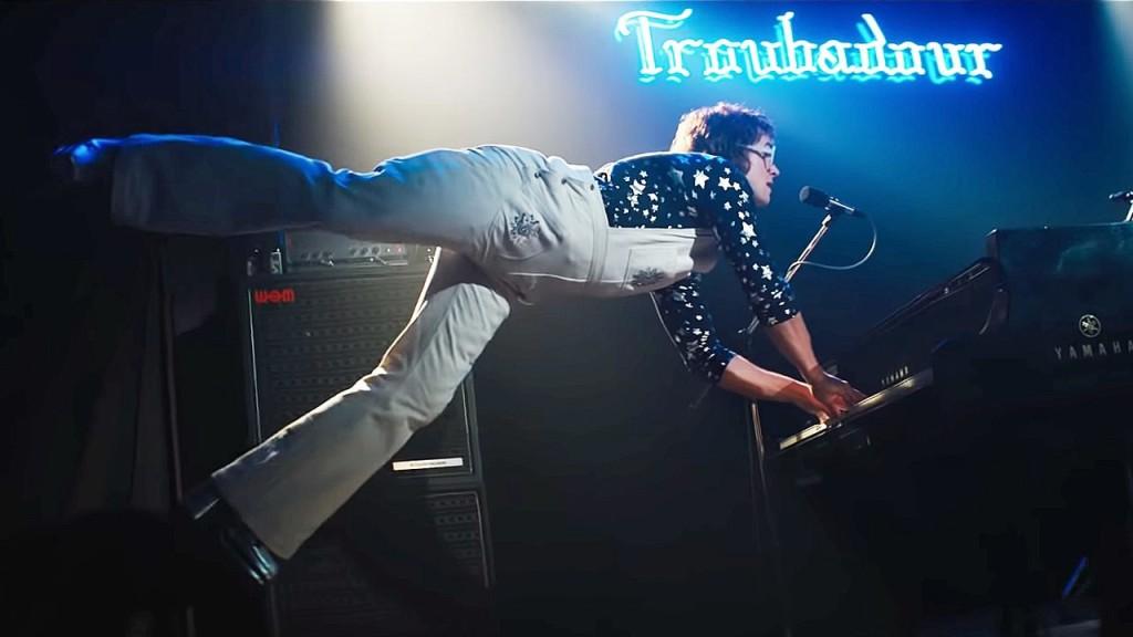 Elton John (Taron Egerton) playing th piano, his feet in the air as he floats up.