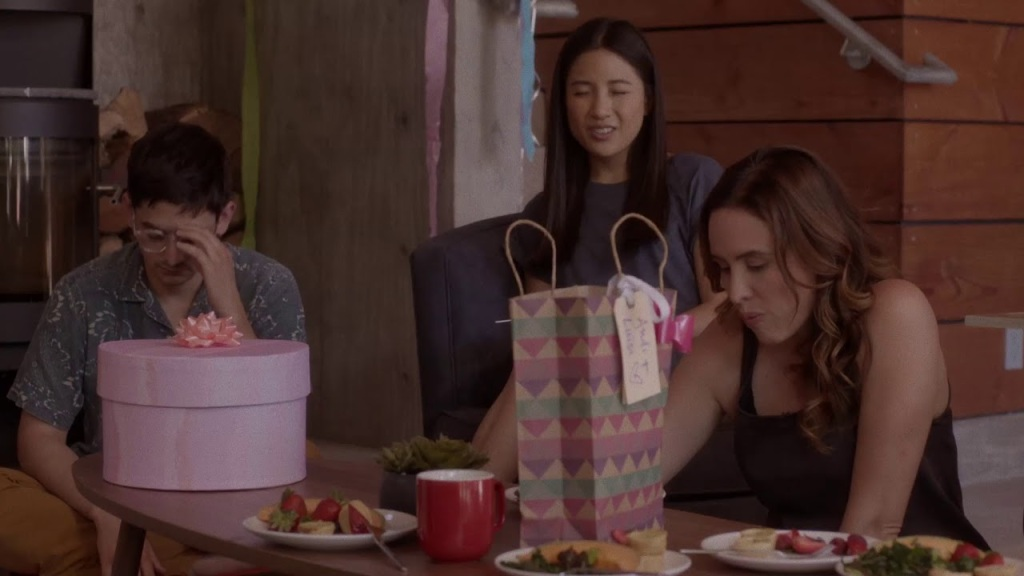 Josh (Josh Fadem), Andi (Constance Wu) and Nikki (Jenée LaMarque) at a table with presents and food.