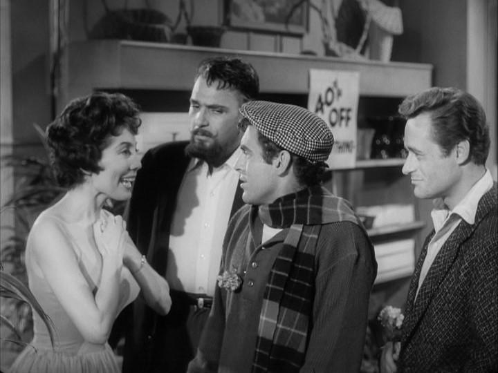 Seymour (Jonathan Haze) telling Audrey (Jackie Joseph) that he named his plant after her, with Gravis Mushnick (Mel Welles) and Fouch (Dick Miller) standing by.