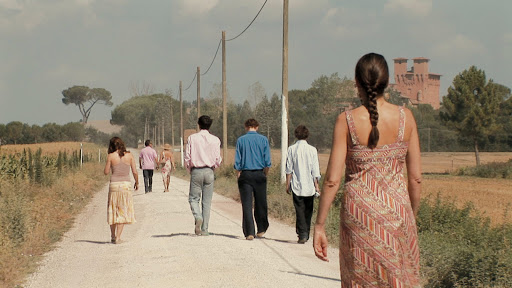The entire group walking down a country road with Anna (Kathryn Worth) trailing behind them on her own.