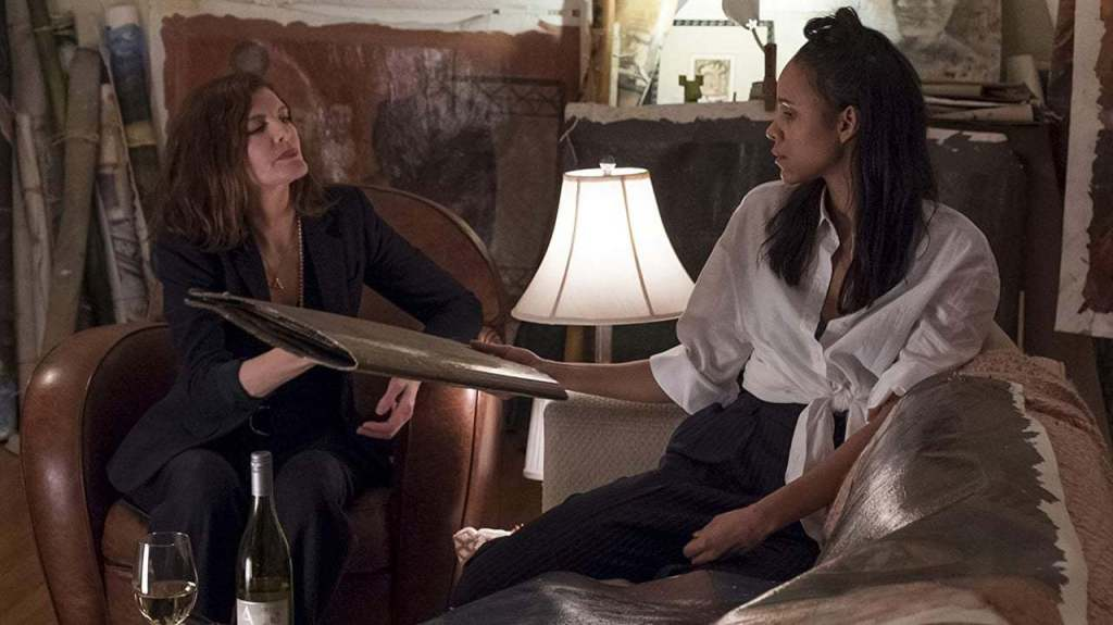 Josephina (Zawe Ashton) handing Rhodora (Rene Russo) a folder with paintings.