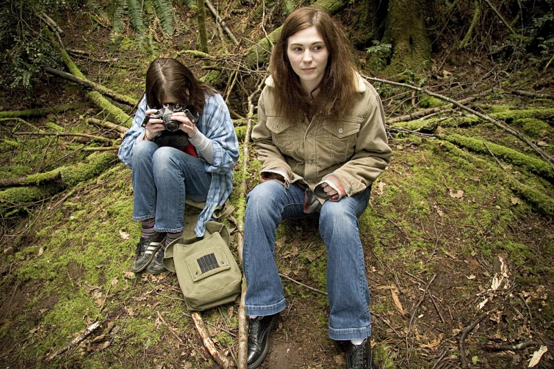 Kate (Amber Hubert) sitting with her 13-year-old self (Maggie Brown) in the woods.