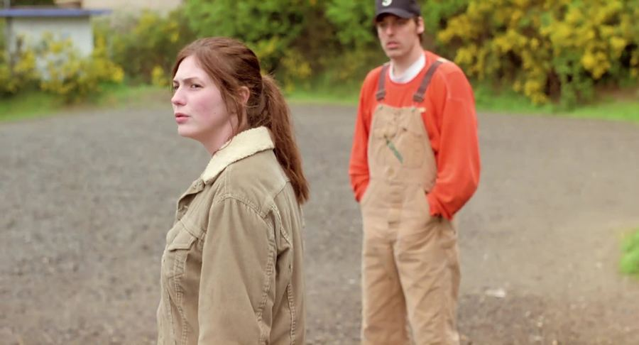Kate (Amber Hubert) with a confused face, a guy standing behind her.