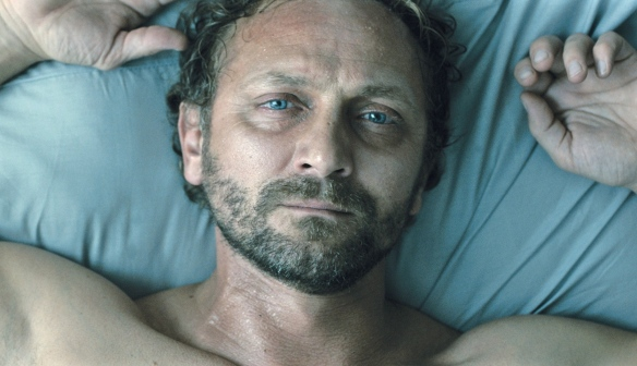 Adam (Andrzej Chyra) lying sweat-soaked in bed.