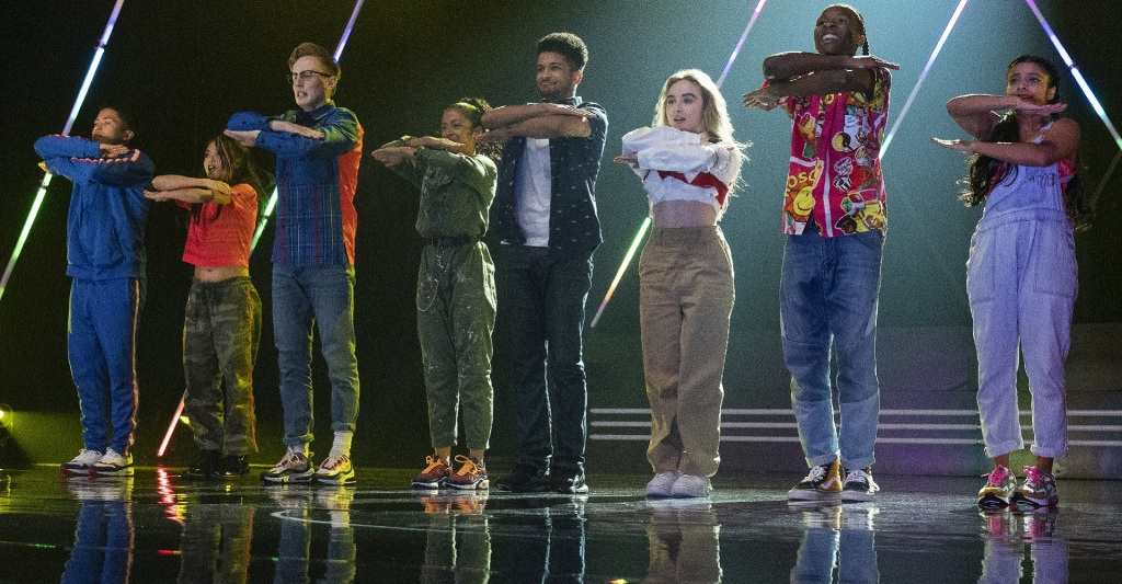 Quinnt (Sabinra Carpenter) and her dance crew, including instructor Jake (Jordan Fisher) during their performance.