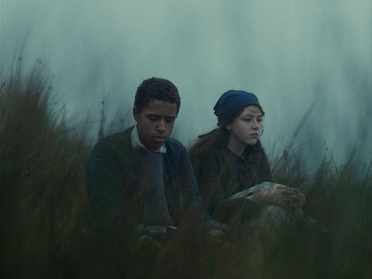 Heathcliff (Solomon Glave) and Catherine (Shannon Beer) sitting in the moors.