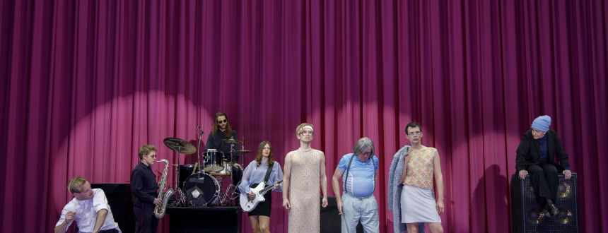 The cast, including a small band, standing in front of a huge pink curtain.