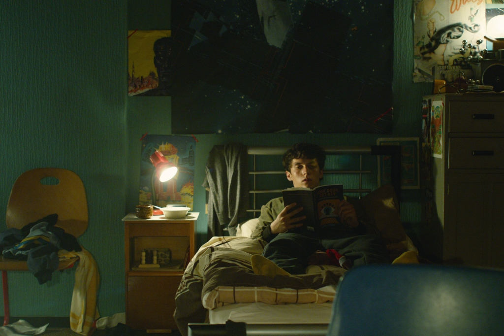 Stefan (Fionn Whitehead) reading the novel Bandersnatch in his room.