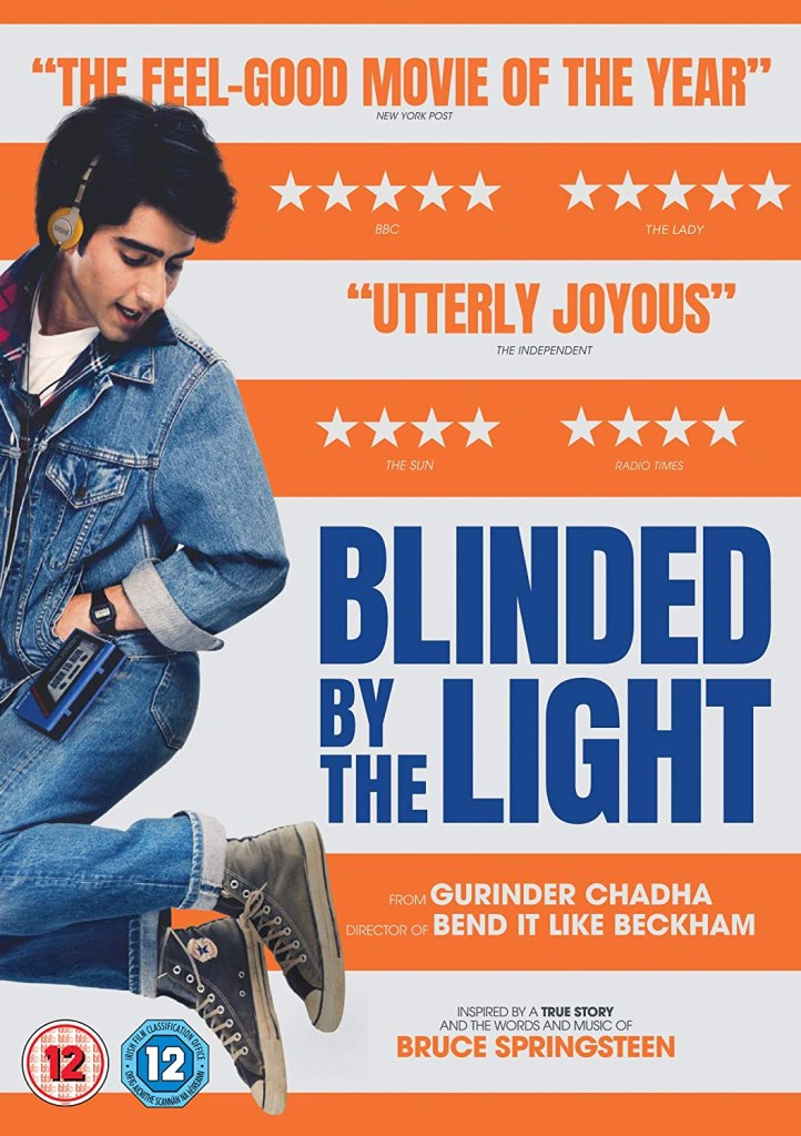 The film poster showing Javed (Viveik Kalra) mid-jump in front of a orange-and-white striped background, reminiscent of Bruce Springsteen's Born in the USA album cover.