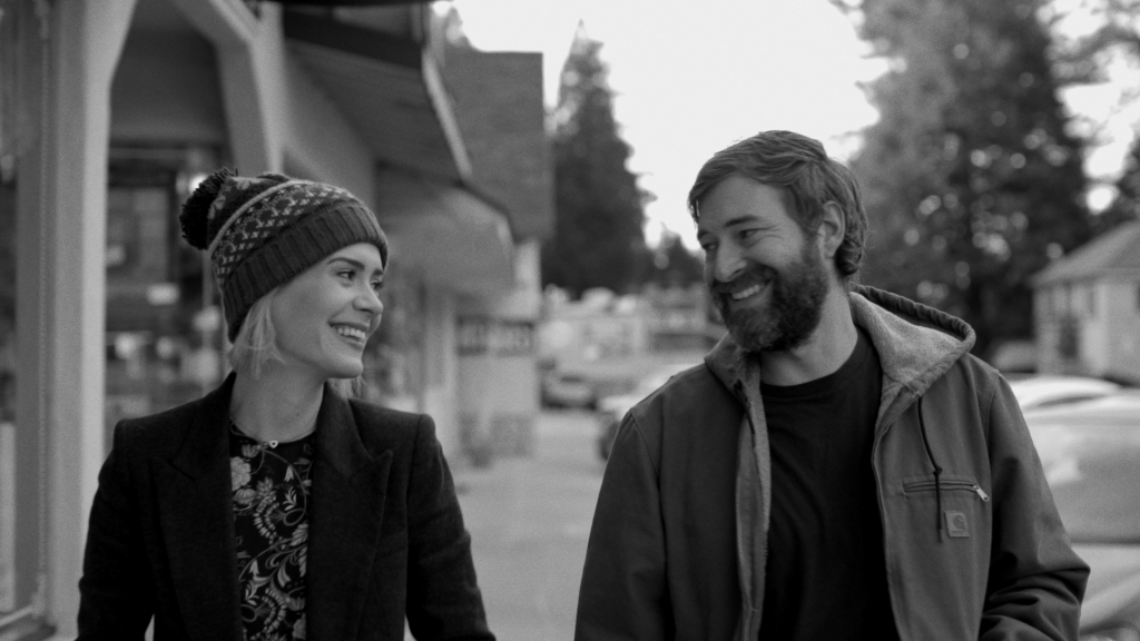 Amanda (Sarah Paulson) and Jim (Mark Duplass) walking down a street smiling at each other.