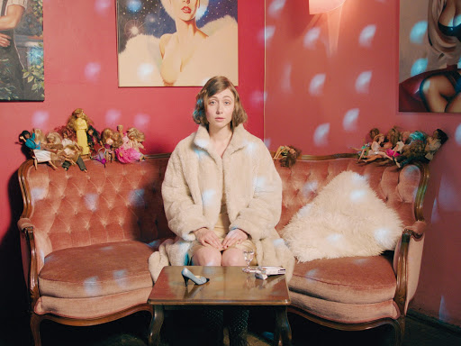 The Melancholic Girl (Marie Rathscheck) sitting on a sofa, lit by disco lights, waiting.