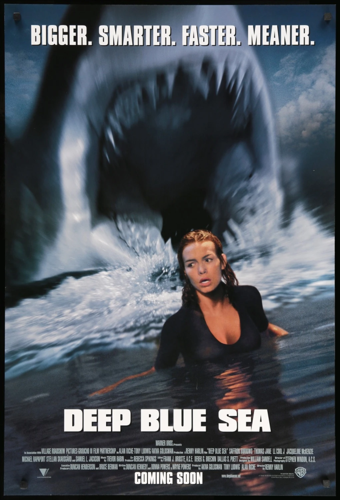 The film poster showing a shark with his mouth open wide behind Susan (Saffron Burrows), up to her breast in water.