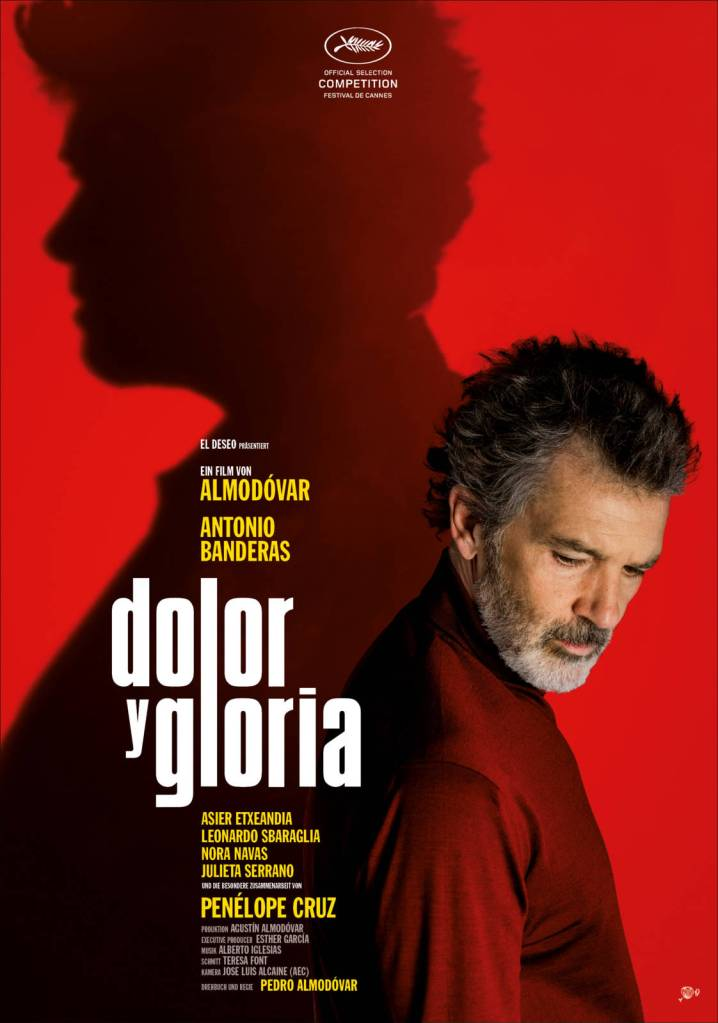 The film poster showing Salvador (Antonio Banderas) in profile, looking down and right. Behind him on the red background is a shadow that is similar to him but is looking straight ahead to the left.