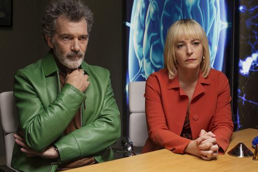 Salvador (Antonio Banderas) and Mercedes (Nora Navas) sitting at a table, looking worried.