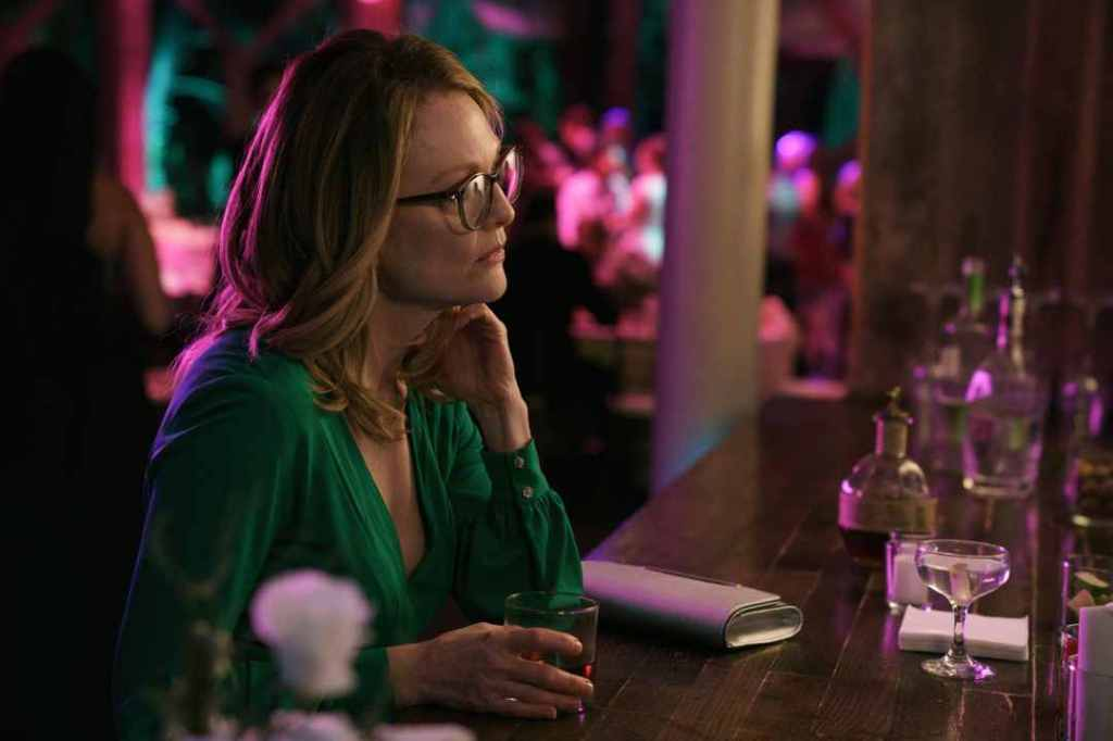Gloria (Julianne Moore) sitting at a bar with a drink.