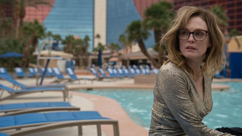 Gloria (Julianne Moore) next to a hotel pool. looking like she spent the night partying.