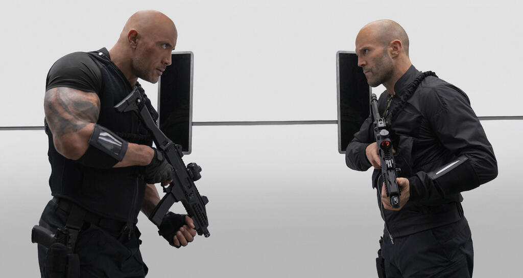 Hobbs (Dwayne Johnson) and Shaw (Jason Statham) facing each other with automated weapons in hand.