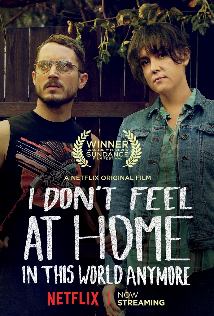The film poster showing Tony (Elijah Wood) and Ruth (Melanie Linskey) standing with very serious looks in front of a garden fence.