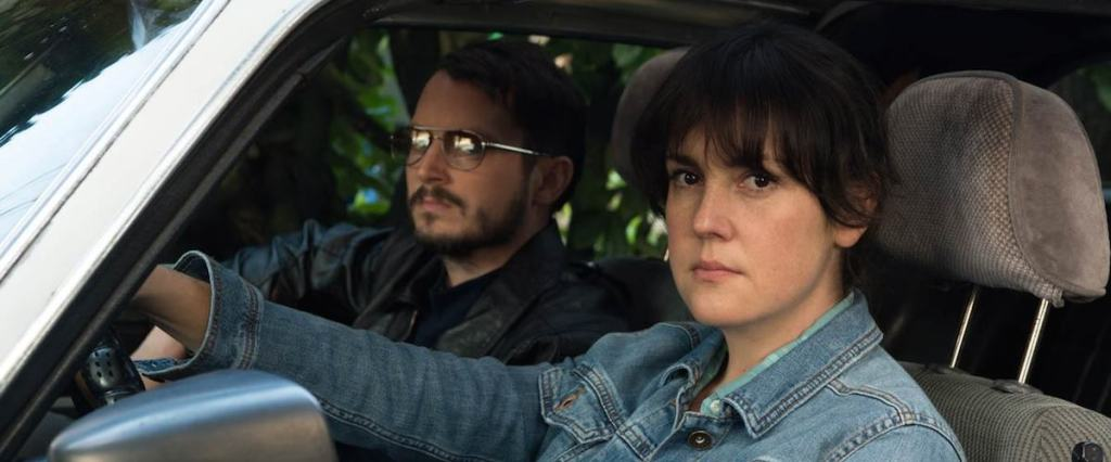 Tony (Elijah Wood) and Ruth (Melanie Linskey) observing something from the car.