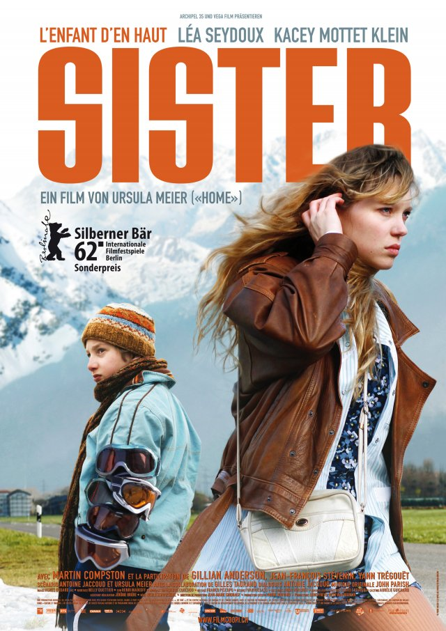 The film poster showing Simon (Kacey Mottet Klein) with several pairs of ski goggles strapped to his arm and Louise (Léa Seydoux) with their backs to each other.