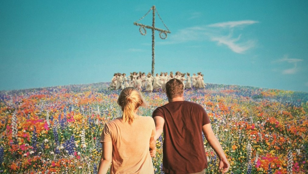 Christian (Jack Reynor) leading Dani (Florence Pugh) across a meadow full of flowers towards a group of people dancing around a huge wooden pole, all dressed in white.