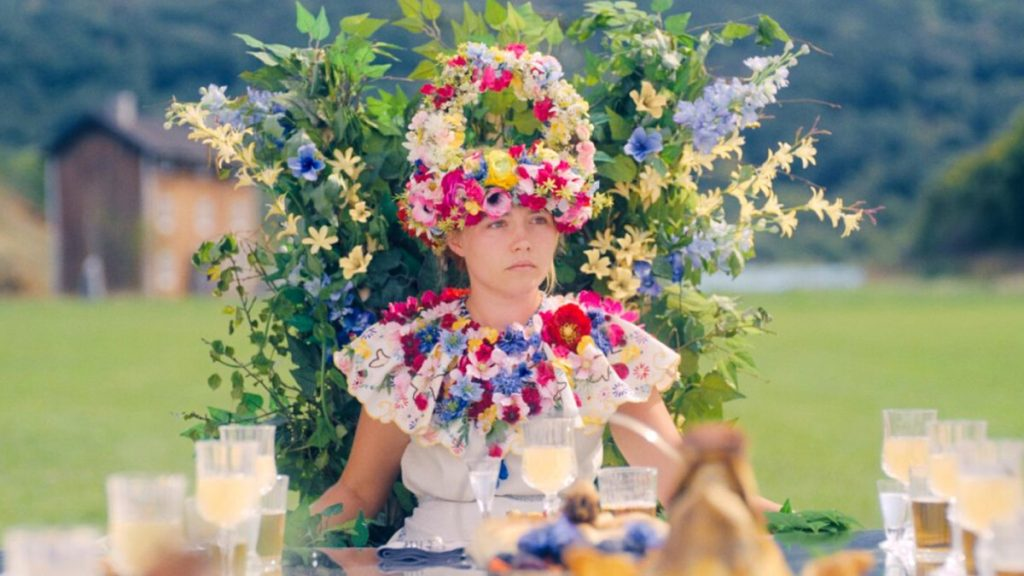 Dani (Florence Pugh) wearing an elaborate flower crown, sitting on a throne decorated with flowers and leaves.