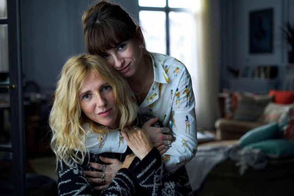 Jade (Thaïs Alessandrin) hugging Héloïse (Sandrine Kiberlain) from behind.