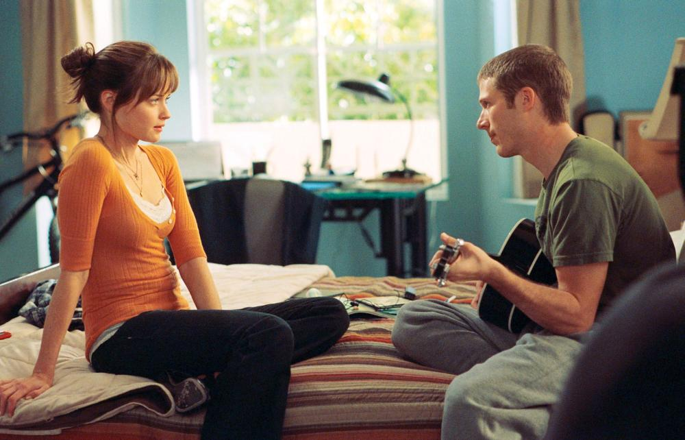 Ryden (Alexis Bledel) sitting on the bed with her best friend Adam (Zach Gilford) while he plays the guitar.
