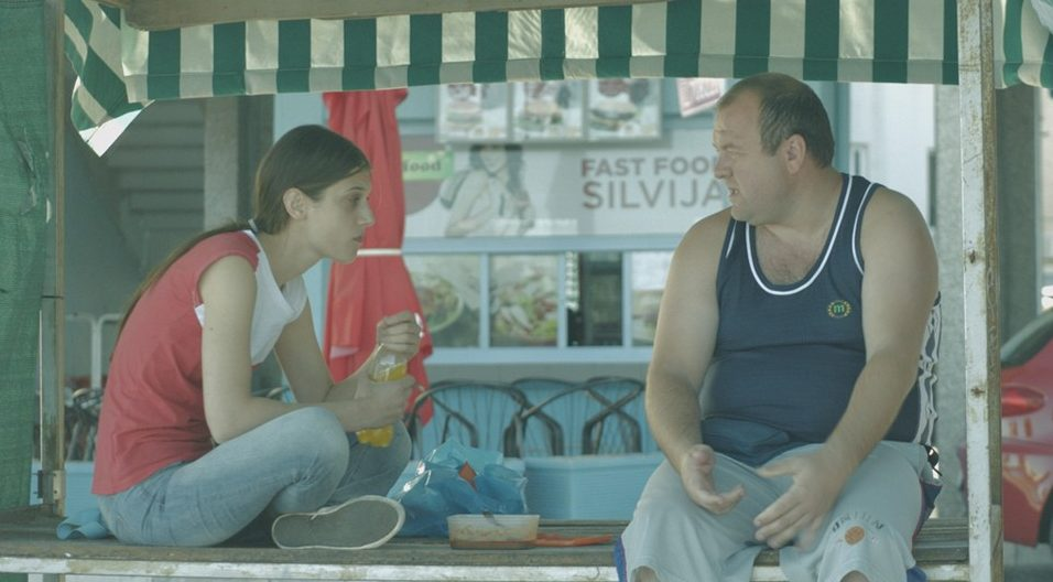 Marijana (Mia Petricevic) eating lunch with her brother Zoran (Niksa Butijer) at a street stand.