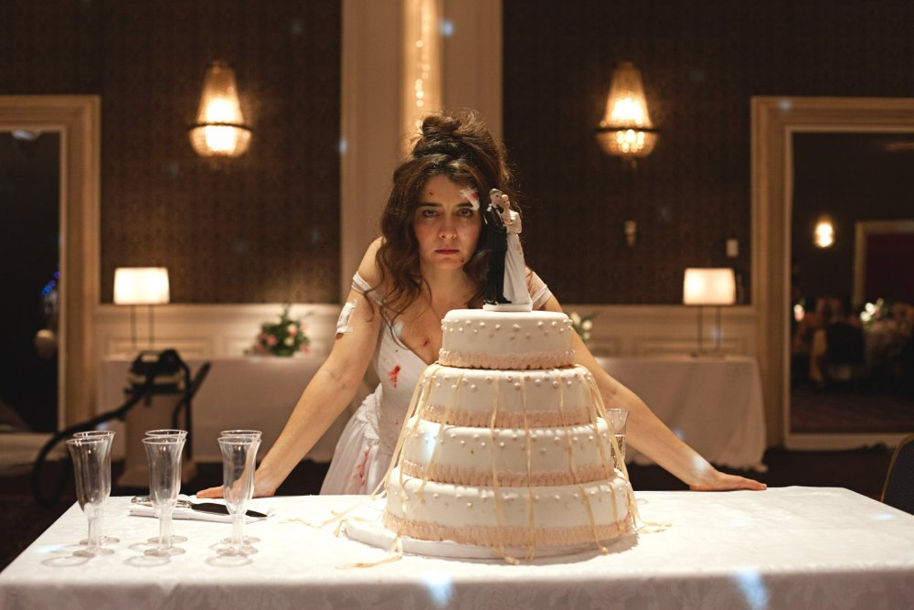 Roman (Erica Rivas) in her bridal gown, looking disheveled, a couple of blood stains on her, standing behind the wedding cake.