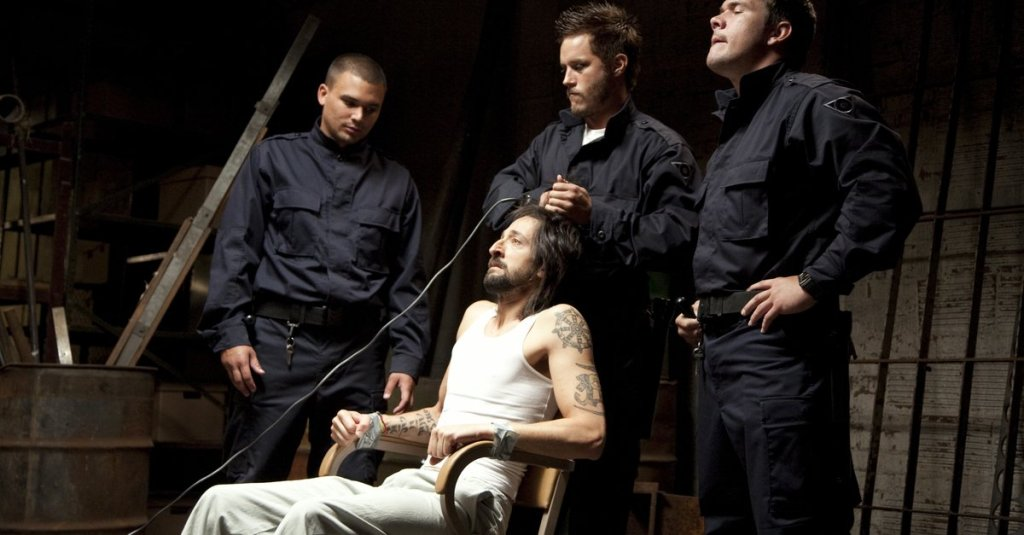 """""""Guard"""" Helweg (Travis Fimmel) shaving Travis' (Adrien Brody) head while he is tied to a chair."""