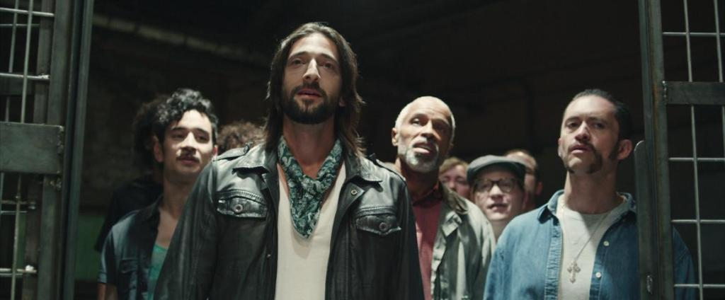 """Travis (Adrien Brody) leading the other """"prisoners"""" into the prison."""