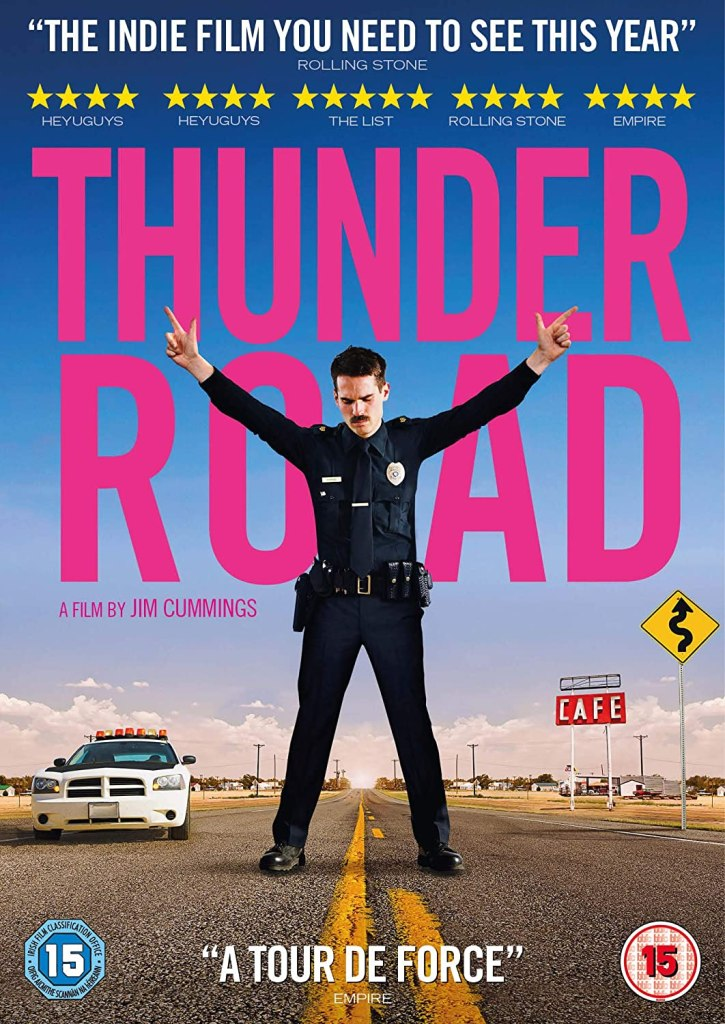 The film poster showing Jim Arnaud (Jim Cummings) in his police uniform stnading in the middle of a street, fingergunning up to the sky with both hands.