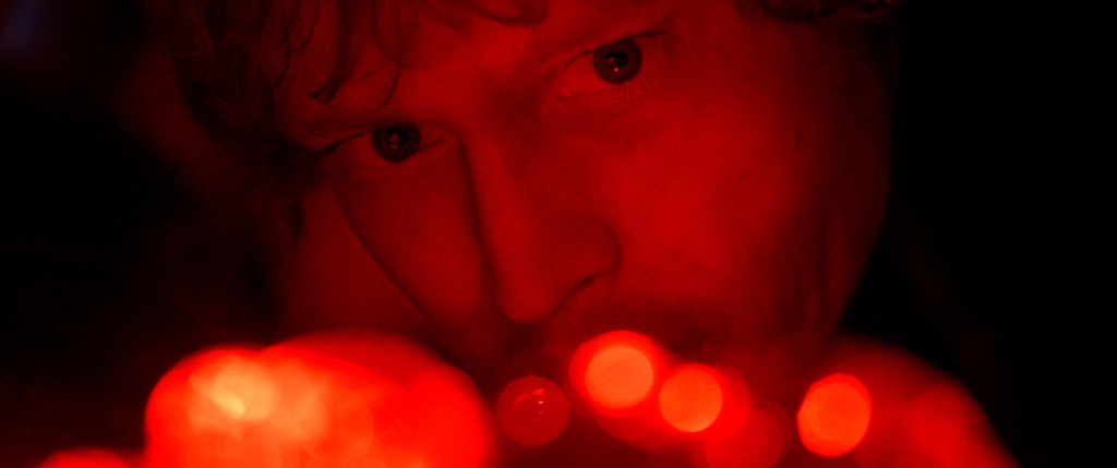 Norman (Caleb Landry Jones) drenched in red light.