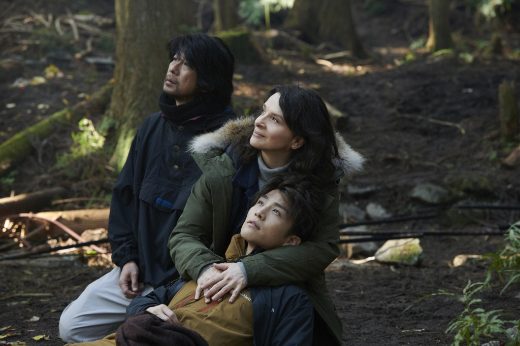 Jeanne (Juliette Binoche), Satoshi (Masatoshi Nagase) and Rin (Takanori Iwata) in the forest, with Jeanne cradling Rin in her lap.