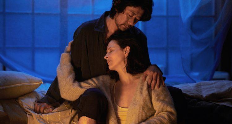 Satoshi (Masatoshi Nagase) cradling Jeanne (Juliette Binoche) in his lap.
