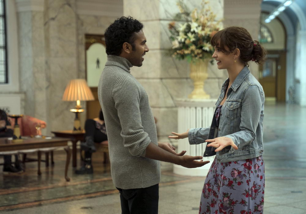 Jack (Himesh Patel) and Ellie (Lily James) getting ready to hug each other as they meet in a hotel lobby.
