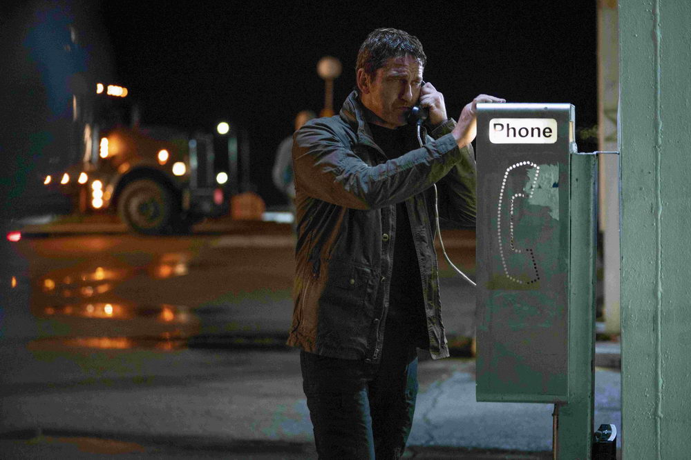 Mike Banning (Gerard Butler) using a payphone, looking disheveled.