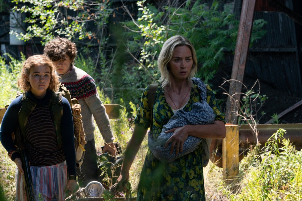 Evelyn (Emily Blunt) carrying a baby, Regan (Millicent Simmonds) and Marcus (Noah Jupe) are making their way through an unkempt area.