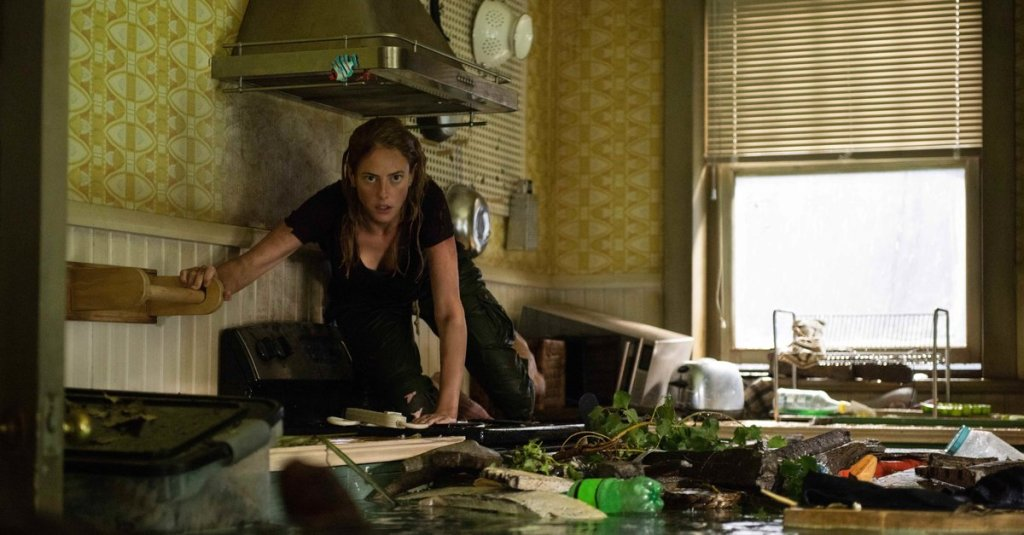 Haley (Kaya Scodelario)  crossing on the countertops through a flooded kitchen.