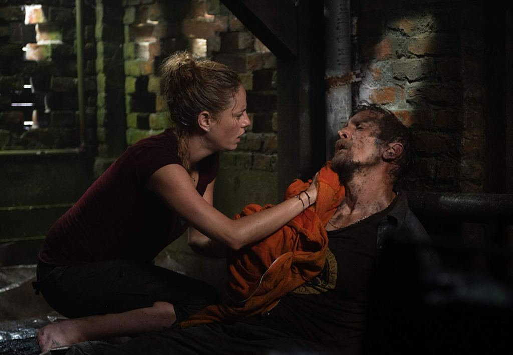 Haley (Kaya Scodelario) wiping her hurt father Dave's (Barry Pepper) face in the basement.