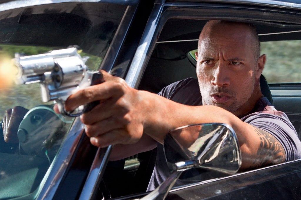 The Driver (Dwayne Johnson) shooting his gun out a car window while driving.